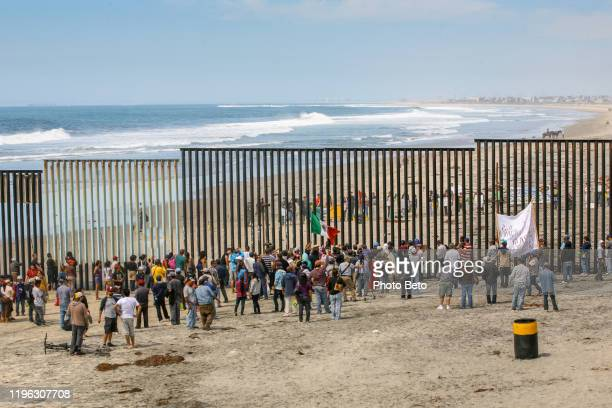 dozens of migrants and workers on the sides of the us-mexico border wall in tijuana beach - refugee stock pictures, royalty-free photos & images
