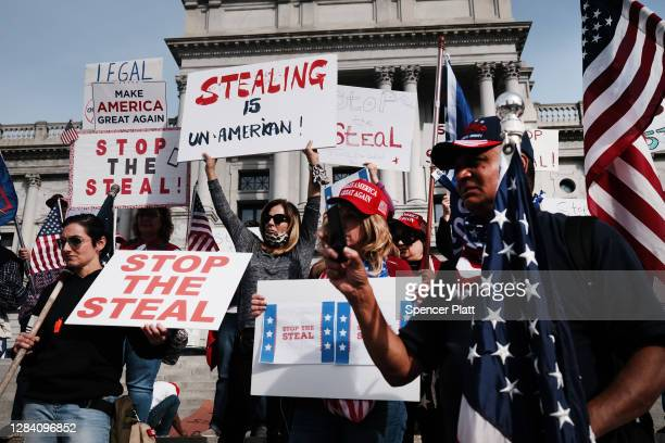 Dozens of people calling for stopping the vote count in Pennsylvania due to alleged fraud against President Donald Trump gather on the steps of the...