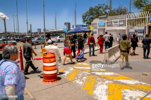 dozens of people cross the us-mexico border at the san ysidro port of entry in tijuana - crossing sign stock pictures, royalty-free photos & images