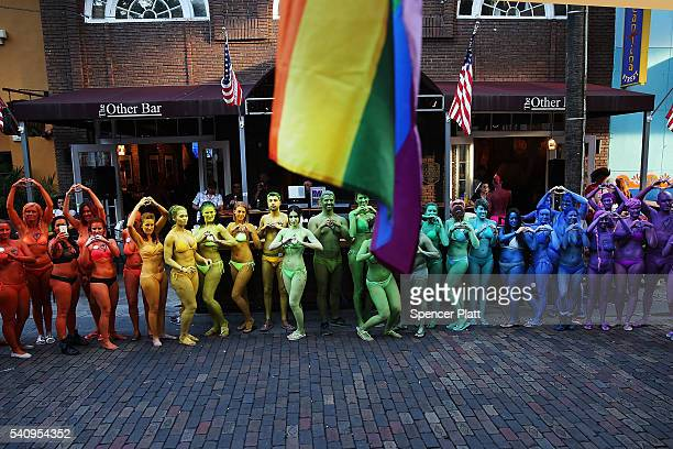 Dozens of people stand outside of a bar while painted in the colors of the rainbow flag to show their solidarity with the LGBT community following...