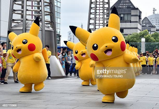 Dozens of Pikachu characters the famous character of Nintendo's videogame software Pokemon march at the Landmark Plaza shopping mall in Yokohama...
