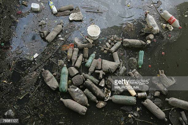 Dozens of plastic bottles originated from trash float over the highly polluted waters of the Tiete river the day after heavy rains left at least 40...