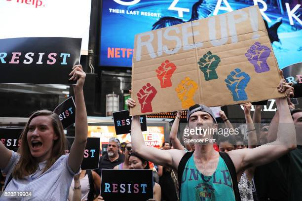 Dozens of protesters gather in Times Square near a military recruitment center to show their anger at President Donald Trump's decision to reinstate...