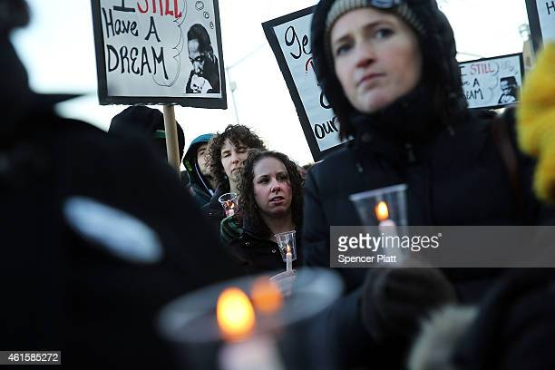 Dozens of protesters hold a demonstration and candlelight vigil outside of the 120th Police Precinct Station in memory of Eric Garner on January 15...