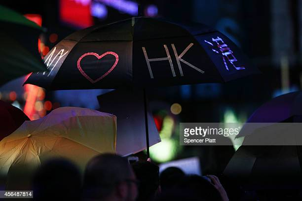 Dozens of protesters hold up umbrellas while demonstrating in New York's Times Square to show solidarity with pro democracy events in Hong Kong on...