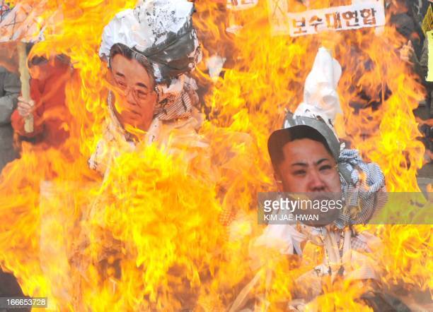 Dozens of South Korean activists burn effigies with the portraits of North Korea's late president Kim IlSung and his grandson and current leader Kim...