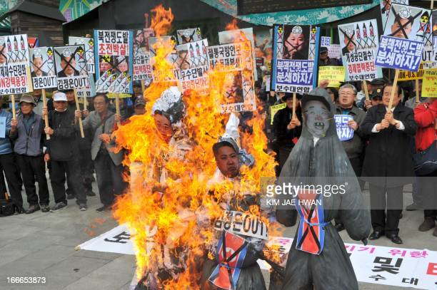 Dozens of South Korean activists burn effigies with the portraits of North Korea's late president Kim IlSung his grandson and current leader Kim...