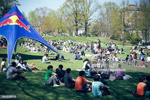 Dozens of students huddle and sunbathe on the grassy Beach, with drinks all around and a large Red Bull tent to the left, during Spring Fair, a...