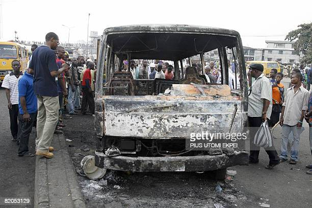 Dozens of sympathisers look at the burnt coaster bus where the occupants mostly workers died in Lagos on July 24 2008 A petrol tanker burst into...