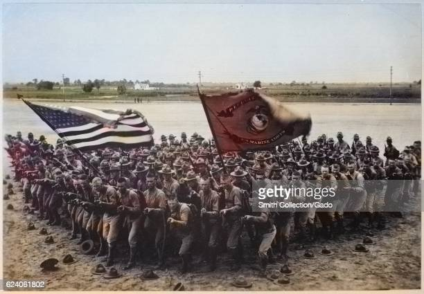 Dozens of United States Marines clustered by the shore carrying flags for a recruitment advertisement during World War I 1918 Image courtesy National...