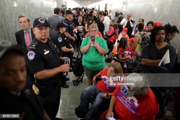 Dozens of U.S. Capitol Police officers line the hallway and keep watch on people waiting to attend the Senate Finance Committee hearing about the...