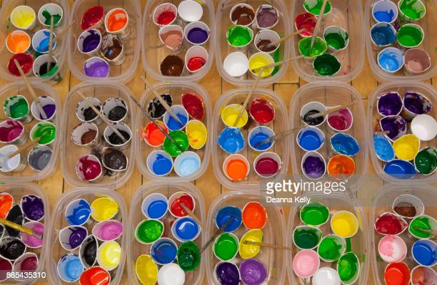 Dozens of well used paint cups and paintbrushes with vividly colored paint, overhead view