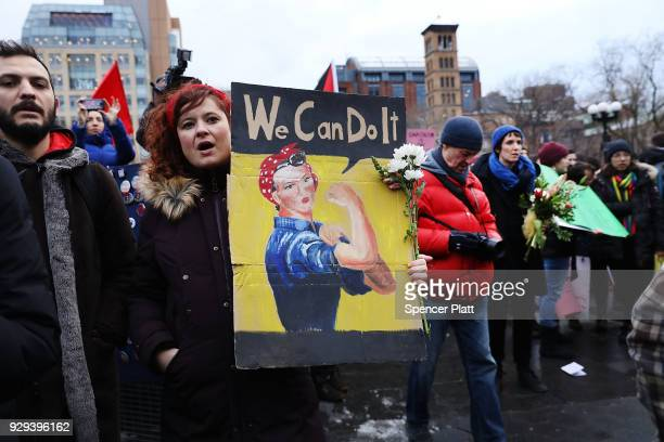 Dozens of women and men attend a rally and march in Washington Square Park for international Women's Day on March 8 2018 in New York City Around the...