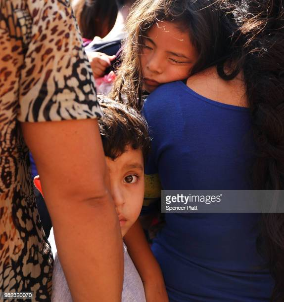 Dozens of women men and their children many fleeing poverty and violence in Honduras Guatamala and El Salvador arrive at a bus station following...