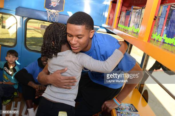 Dozier of the Oklahoma City Thunder helps students select a free book on the Rolling Thunder Book Bus in conjunction with the NBA Read to Achieve...