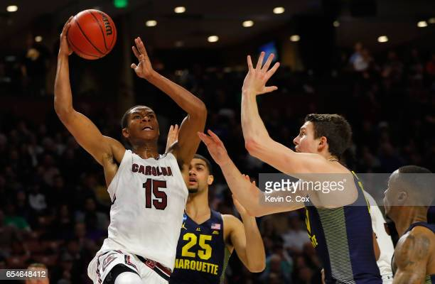 Dozier of the South Carolina Gamecocks drives against Haanif Cheatham and Matt Heldt of the Marquette Golden Eagles in the first half during the...