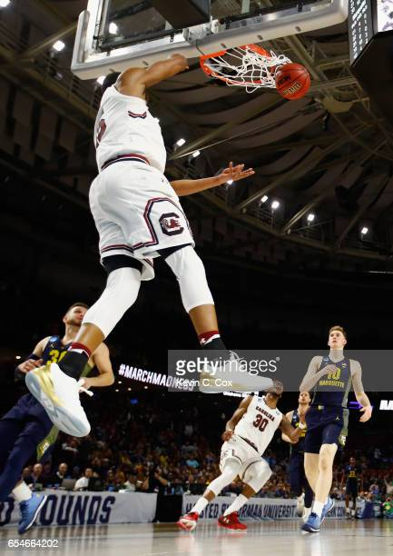 Dozier of the South Carolina Gamecocks dunks against Andrew Rowsey of the Marquette Golden Eagles in the second half during the first round of the...