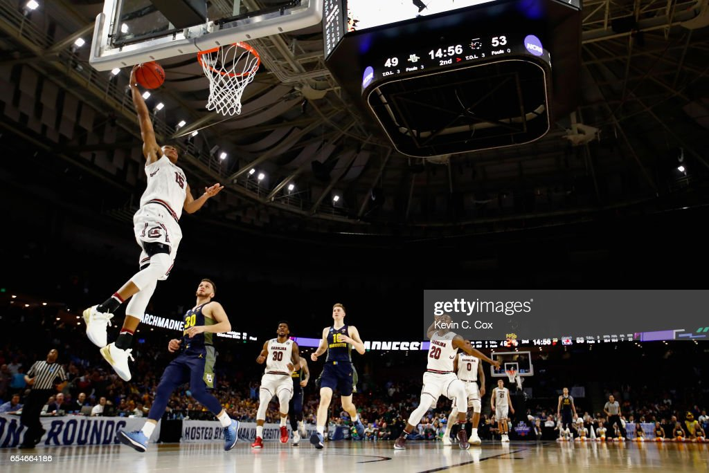 PJ Dozier #15 of the South Carolina Gamecocks goes up for a shot against Andrew Rowsey #30 of the Marquette Golden Eagles in the second half during the first round of the 2017 NCAA Men's Basketball Tournament at Bon Secours Wellness Arena on March 17, 2017 in Greenville, South Carolina. The South Carolina Gamecocks won 93-73.