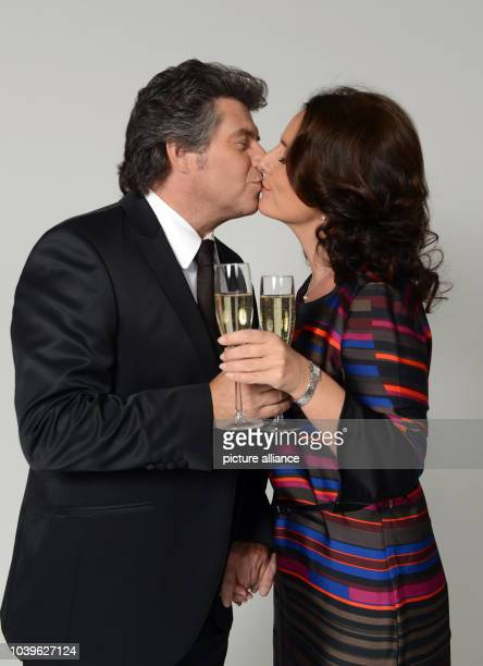dpaExclusive Austrian television presenter and singer Andy Borg and his wife Birgit kiss each other as they cheer with a glass of sparkling wine...