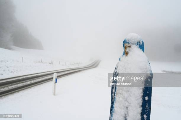 Dpatop - 01 December 2020, Baden-Wuerttemberg, Ravensburg: A figure belonging to a snow-covered field cross stands not far from the community of...