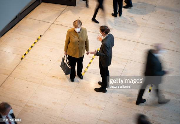 Dpatop - 04 March 2021, Berlin: Chancellor Angela Merkel and Karl Lauterbach, SPD health expert, talk on the sidelines of the 215th session of the...