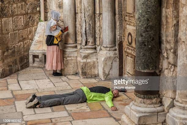 Dpatop - 05 April 2020, Israel, Jerusalem: A woman prays as a man lies outside the closed door of the Church of the Holy Sepulchre during the...