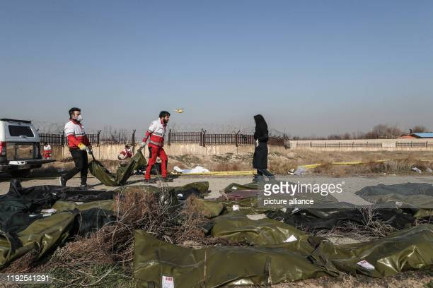 dpatop 08 January 2020 Iran Shahedshahr Rescue workers carry the body of a victim of a Ukrainian plane crash A Ukrainian airplane carrying 176 people...