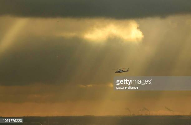 dpatop 11 December 2018 Hessen Frankfurt/Main An emergency doctor helicopter flies in front of a dark cloud wall through the few sunbeams that can...