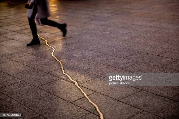 A woman walks on the Christmas market at Breitscheidplatz over the 'crack' of the memorial for the victims of the assassination on In December 2016...