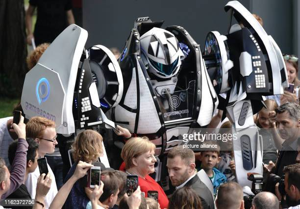 Chancellor Angela Merkel has herself photographed with a robot figure in the Federal Chancellery's courtyard of honour during the Federal...