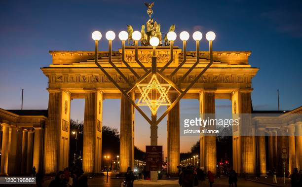 Dpatop - 18 December 2020, Berlin: All nine lights burn at sunset on the Hanukkah candelabra, which stands in front of the Brandenburg Gate. Photo:...