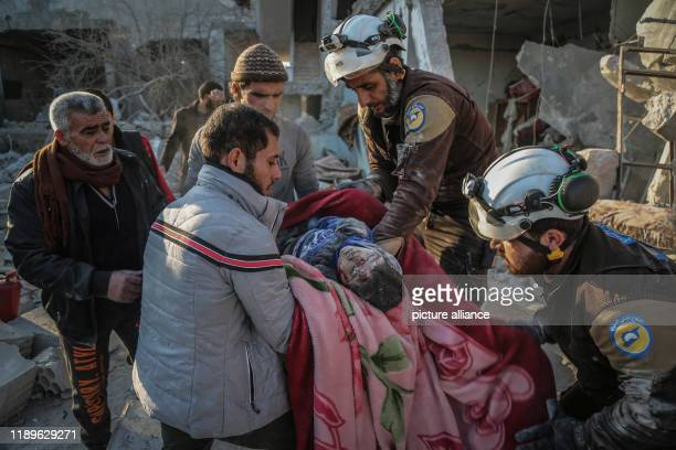 Dpatop - 19 December 2019, Syria, Idlib: Members of the Syrian Civil Defence, also known as the White Helmets, carry the body of a victim from the...