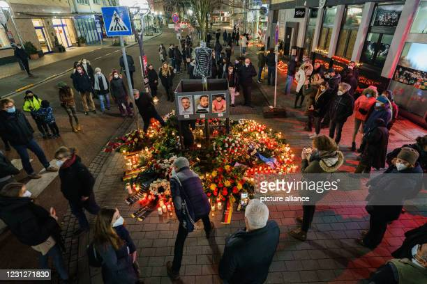 Dpatop - 19 February 2021, Hessen, Hanau: People stand quietly at the time of the crime at the memorial site on Heumarkt, near a crime scene. A...