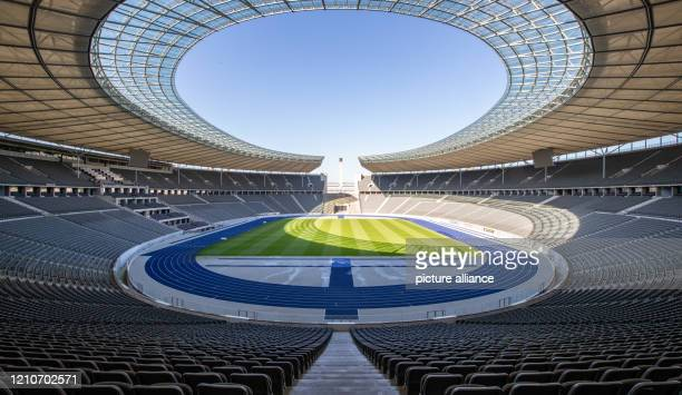 Dpatop - 23 April 2020, Berlin: A view over the Olympiastadion Berlin shows empty tiers and deserted lawns in bright sunshine. Due to measures to...