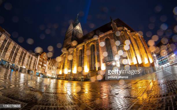 Dpatop - 23 December 2020, Lower Saxony, Hanover: A star is projected onto the tower of the Marktkirche while raindrops bead on the objective lens ....