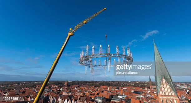 Dpatop - 23 November 2020, Lower Saxony, Lüneburg: A crane lifts the so-called Wichernkranz onto the 56-meter-high water tower of the city. The...