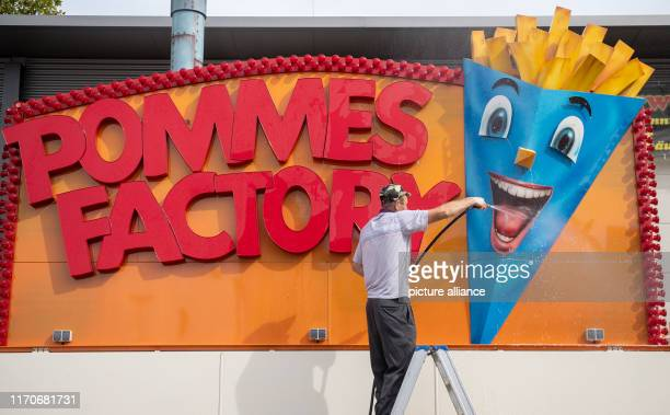 dpatop 24 September 2019 BadenWuerttemberg Before the opening of the 174th Cannstatter Volksfest a man cleans a food stand where French fries are...