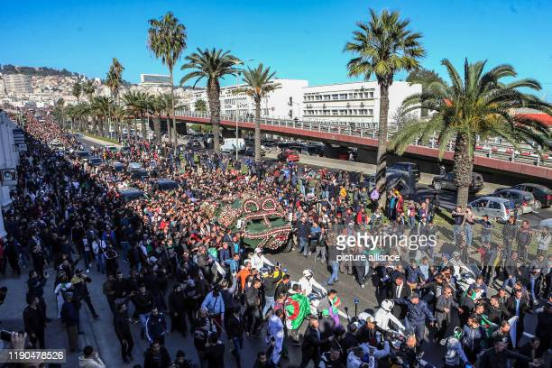dpatop 25 December 2019 Algeria Algiers People gather around an armoured vehicle pulling the flagdraped casket of Algerian Army Chief of Staff Ahmed...