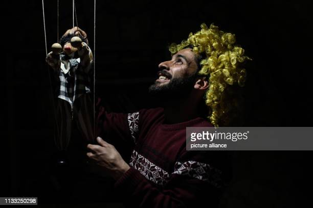 Puppeteer Walid Rashed rehearses a shadow play act with a marionette puppet at his workshop where he prepares for his puppet acts for Syrian children...
