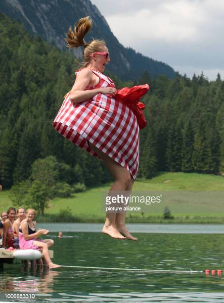 Dpatop - 28 July 2018, Germany, Mittenwald: A participant jumps into the Lautersee during Dirndl flight day. A jury evaluates the jump and the outfit...