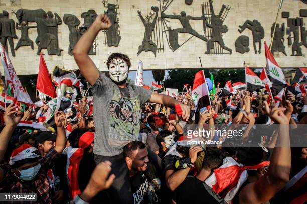 Dpatop - 30 October 2019, Iraq, Baghdad: Iraqi people wave flags and shout slogans during an anti-government demonstration at Liberation Square....
