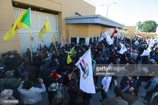 Dpatop - 31 December 2019, Iraq, Baghdad: Protesters hold flags of the powerful militia of Hashd Shaabi during a demonstration inside the US embassy...