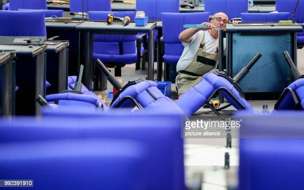 dpatop A man works on the allocation of seats in the plenary hall of the German Parliament in Berlin Germany 17 October 2017 The seating had to...