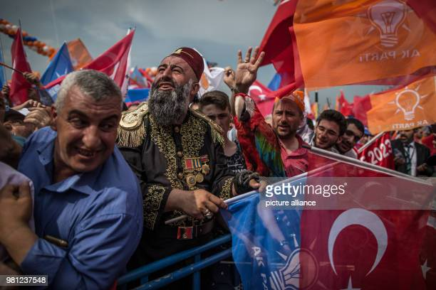 dpatop A supporter of Turkish President Recep Tayyip Erdogan wearing an Ottoman era uniform carries a live parrot while following a speech of the...