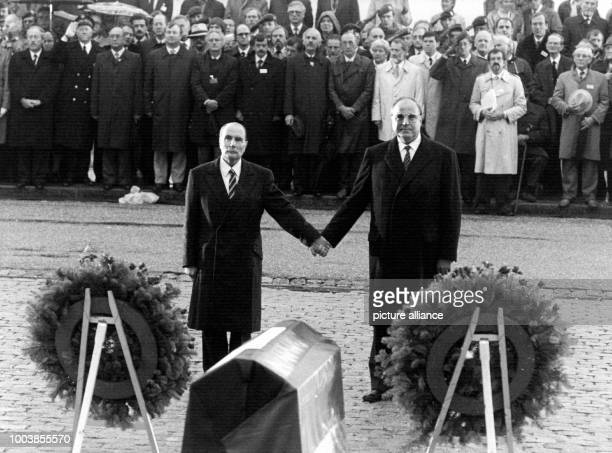 dpatop FILE French President Francois Mitterrand and German chancellor Helmut Kohl take each others hands during a visit to the graves of Verdun...