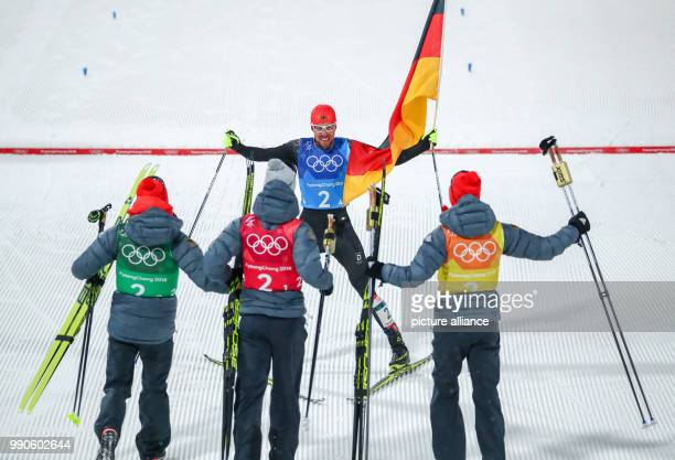 dpatop German gold medallist Johannes Rydzek approaches his teammates while waving the German flag as he crosses the finish line of the men's team...