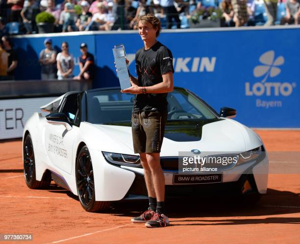 dpatop German Tennis Player Alexander Zverev stands beside his winner's car and holds up the trophy after winning his 2018 BMW Open men's singles...