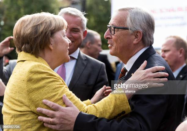 dpatop JeanClaude Juncker the president of the European Commission greets the German chancellor Angela Merkel at a reception marking the German...