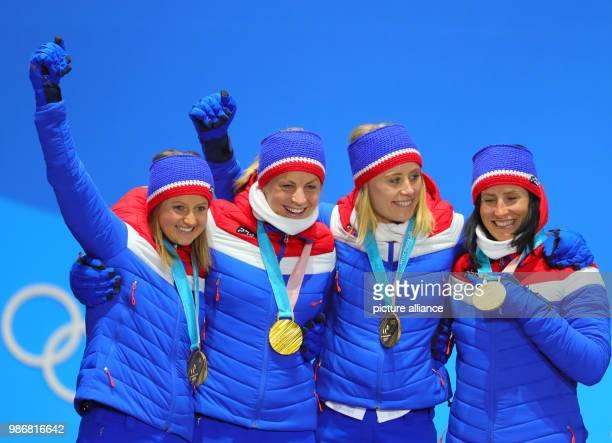 dpatop Norwegian gold medallists Ingvild Flugstad Oestberg Astrid Uhrenholdt Jacobsen Ragnhild Haga and Marit Bjoergen celebrate on the podium during...