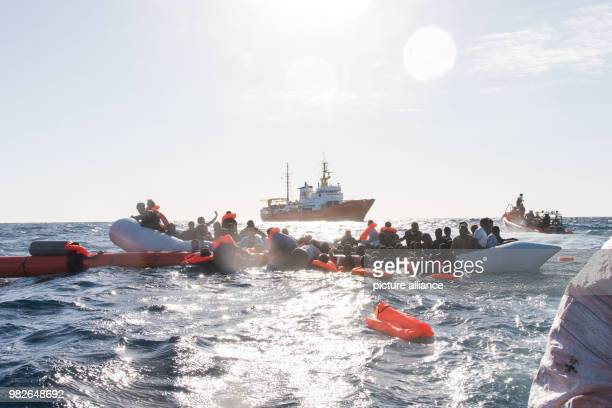 Dpatop - Refugees cling to a rubber dinghy during a rescue operation by the Italian SOSMediterranee aid organization, while attempting to cross over...